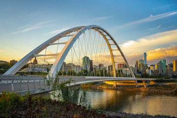 Edmonton, Alberta, Canada skyline at dusk with suspension bridge in foreground and clouds
