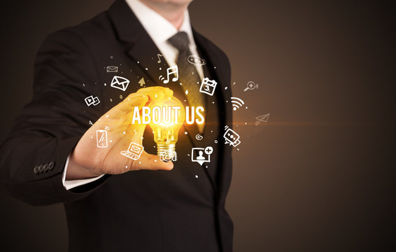 Businessman holding light bulb with ABOUT US inscription, social media concept