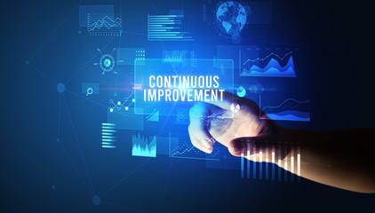 Hand touching CONTINUOUS IMPROVEMENT inscription, new business technology concept