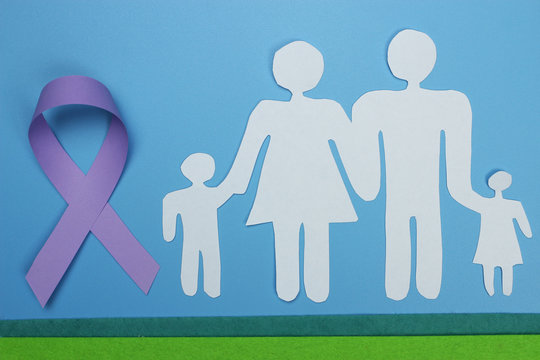 Family cut from paper and purple ribbon for raising awareness on Alzheimer's ' disease.