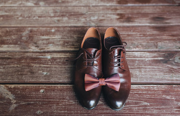 Close-up of leather brown shoes with a bow-tie on a wooden background. Gentleman's, men's set. Business. Wedding shoes, details.