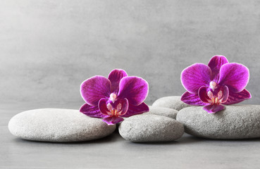 Tuinposter Orchidee Spa stones and orchid flower on the grey background