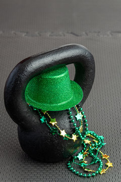 Black iron kettlebell with green leprechaun hat on a black gym floor, green and gold beads, holiday fitness