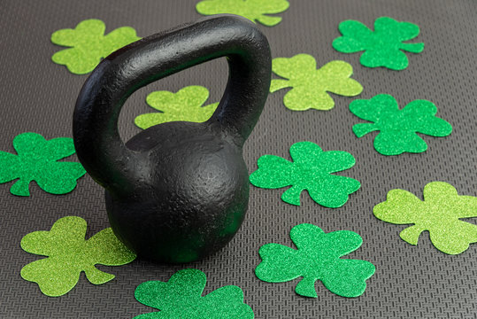 Black iron kettlebell with green shamrocks on a black gym floor, holiday fitness