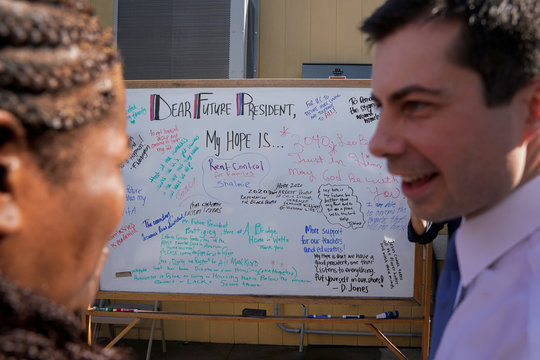 """Democratic 2020 U.S. presidential candidate Pete Buttigieg talks with Anita Hunter in front of a board where residents at """"A Bridge Home"""" transitional housing project wrote what they would want the future president to help with in Los Angeles"""