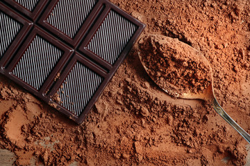 cocoa powder and a bar of dark chocolate. cocoa powder in a spoon. top view