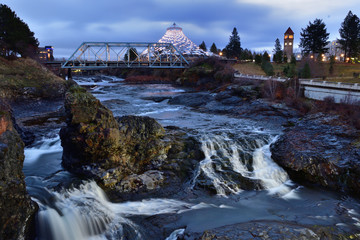 Long exposure, sunrise photo of Spokane Falls on the Spokane River looking over Riverfront Park in downtown Spokane, Washington with a clock tower, bridge and pavilion in the background
