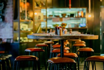 Foto op Canvas Restaurant Inspired by Steampunk design, distressed leather bar stools and vista of service area in a restaurant