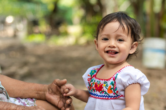 Portrait of a cute child wearing a traditional mexican dress with her grandmother
