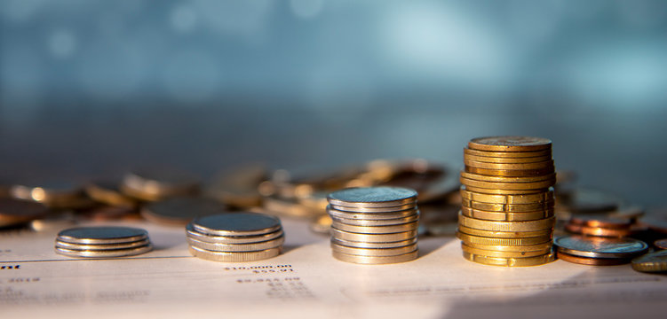 Stacks of coins on top of a bank statement with pile of coins in the background, blue background, banner