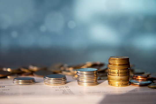 Stacks of coins on top of a bank statement with pile of coins in the background, blue background