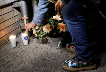 A woman lights a candle outside the Colegio Cervantes private school after a shooting in Torreon