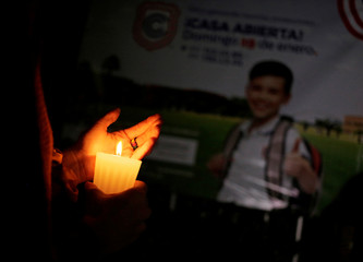 A woman holds a candle outside the Colegio Cervantes private school after a shooting in Torreon