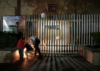 People light candles outside of the Colegio Cervantes private school after a shooting in Torreon