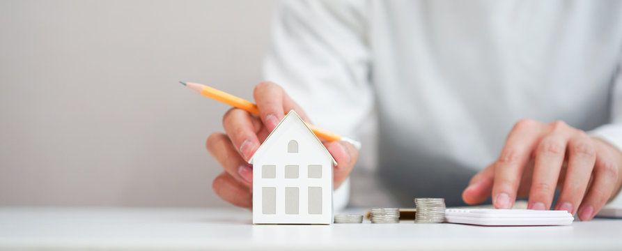 close up young man hand touching house's model for check and summary expense of home loan mortgage for refinance plan , people lifestyle concept