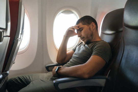 man sleeps in an airplane while sitting in an armchair leaning on his arm. Inconvenient and uncomfortable sleep in the economy class.