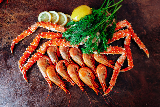 On the table are shrimp, crab, lemon and herbs. Table of reddish color.