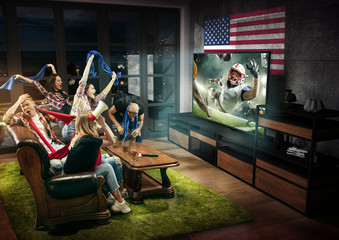 Group of friends watching TV, american football match, championship. Emotional men and women cheering for favourite team, look on fighting for ball. Concept of friendship, sport, competition, emotions