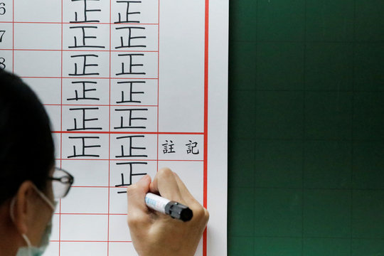 An election official writes down the vote count on a board at a polling station in Kaohsiung