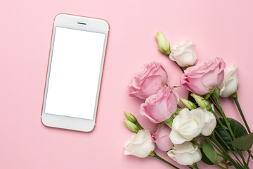 Mobile phone with pink and white roses flowers on pastel background.Minimalistic composition for the holidays,valentines day and womens day.
