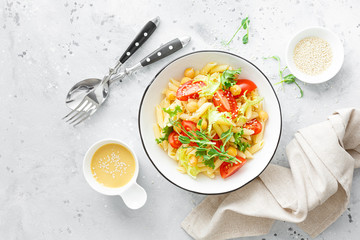 Pasta salad with fresh tomato, chickpea, lettuce and pea sprouts in lunch bowl
