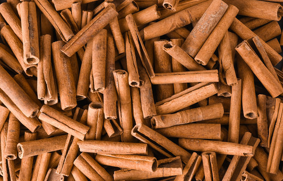 Cinnamon background. Pile of cinnamons stick top view.