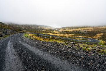 Steep and squiggly gravel road towards the fjords of Mjoifjordur in East Iceland during heavy fog and rain weather. Traveling and explore concept.