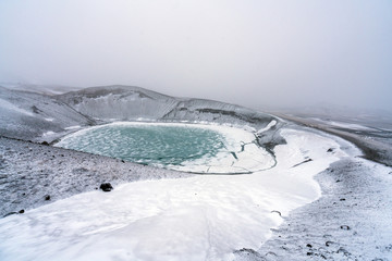 Ovelooking ice covered Viti volcanic crater near Krafla geothermal area in Iceland. Foggy and snow covered landscape with frozen green lake at the bottom. Volcano, energy and weather concept.