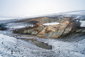 Ice and snow covered ground in Krafla geothermal area near the Viti crater and Lake myvatn in the Icelandic countryside. Volcanic crater and colorful textured volcanic ash and sand spread around.