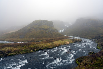 Klifbrekkufossar waterfall in the eastern part of Iceland during rainy and foggy weather. River infront with waterfall cascade in the background.