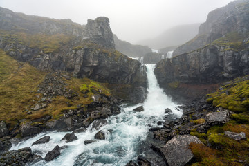 Klifbrekkufossar waterfall in the eastern part of Iceland during rainy and foggy weather. Moss covered landscape and basalt rocks. Icelandic and weather concept.