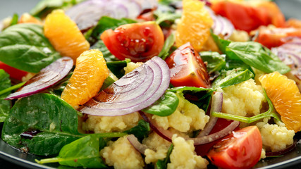 Vegetable Millet salad with red onion, cherry tomatoes, spinach, tangerine and clementine dressing. healthy food