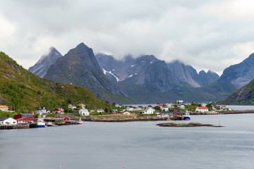 The city of Reine in Lofoten/Norway. Long exposure shot with overcast scenery. Snow covered mountains in the background. Traveling and Norwegian concept.