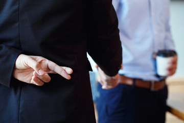 Business partners shaking hand making a deal but Business man holding crossed fingers behind back, Betray concept.