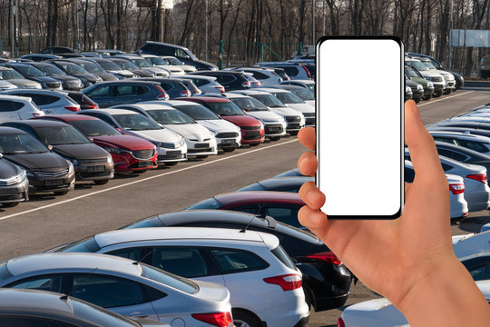 Hand with phone on a background of rows of cars. Car sales.