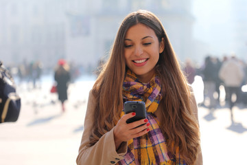 Portrait of beautiful smiling young woman texting on mobile phone outdoor with blurred people on street background, selective focus.
