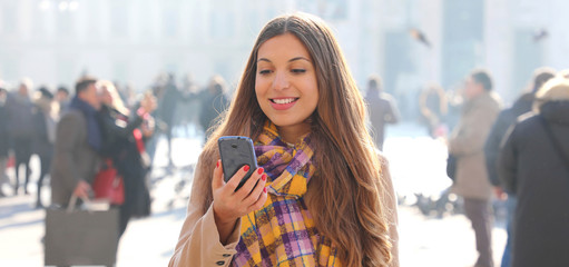 Smiling young woman reading messages on mobile phone outdoor with blurred crowd of people on street background, selective focus. City lifestyle people technology panoramic banner view.