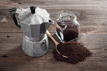 still life photography : ground coffee on old wooden table with old Italian style espresso maker (moka pot)