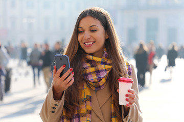 Portrait of young beautiful business woman walking on city street with mobile phone and take away coffee outdoor with blurred people on street background.