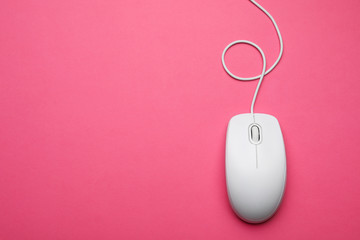 Wired computer mouse on pink background, top view. Space for text
