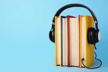 Books and modern headphones on light blue background. Space for text