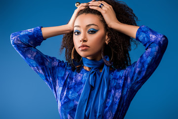 stylish african american woman in dress looking at camera isolated on blue