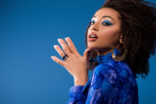stylish african american woman in dress with makeup looking at camera isolated on blue