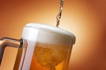 Obraz Kufel z piwem i spływająca piana na złocistym tle - fototapety do salonu