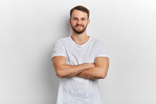 man in stylish T- shirt standing with crossed arms isolated on white background. close up portrait. sportsman having rest, personal trainer looking at the camera, waiting for students to work out