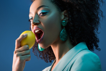 attractive african american woman with braces eating lemon isolated on blue Wall mural