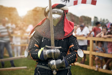 Man in knight costume holding sword.