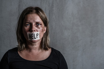 "Beaten up woman victim of domestic violence and abusewith covered her mouth taped with the inscription ""help"". Empty space for text"