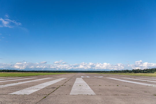 The runway of a rural small airfield against a blue sky