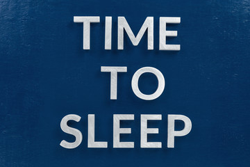 the words time to sleep laid by white silver metal letters on classic blue background in flat lay central composition